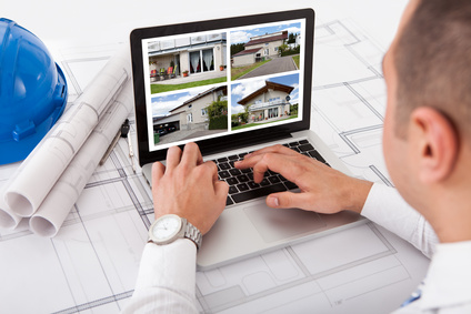 Architect Looking At Designs Of House On Laptop