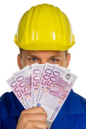 Ein Arbeiter in einem Gewerbebetrieb ( Handwerker ) mit Geldscheinen in der Hand